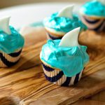 Celebrate Shark Week in the best way possible, with Shark Cupcakes! Moist vanilla cupcakes filled with strawberry jam and topped with the creamiest frosting. Decorated with a shark fin.