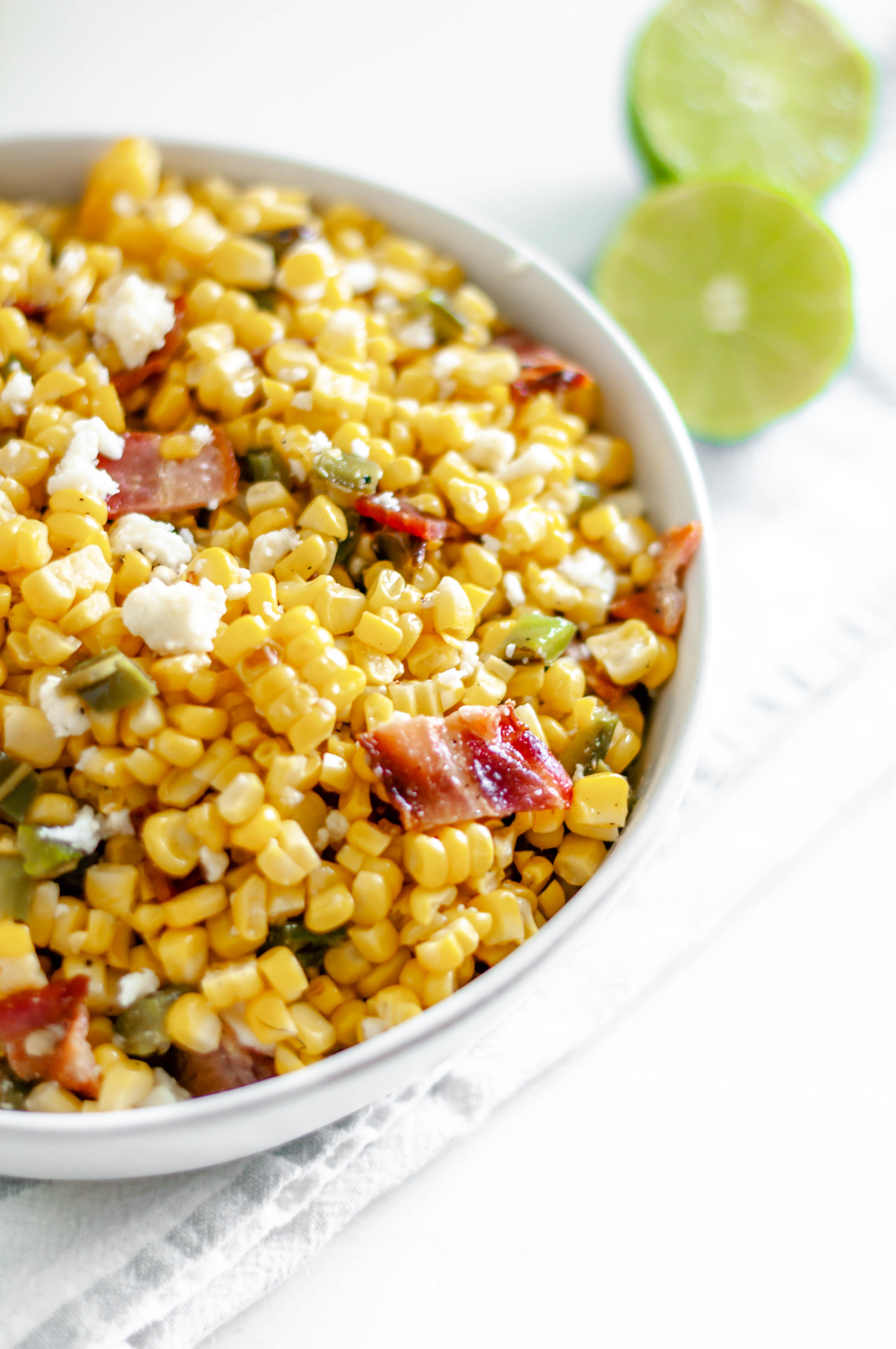 This Grilled Corn Salad with Bacon and Jalapeno is your next potluck dish. Sweet grilled corn, smoky bacon, spicy jalapeno and a bright lime dressing. The perfect addition to any summer barbecue or potluck.