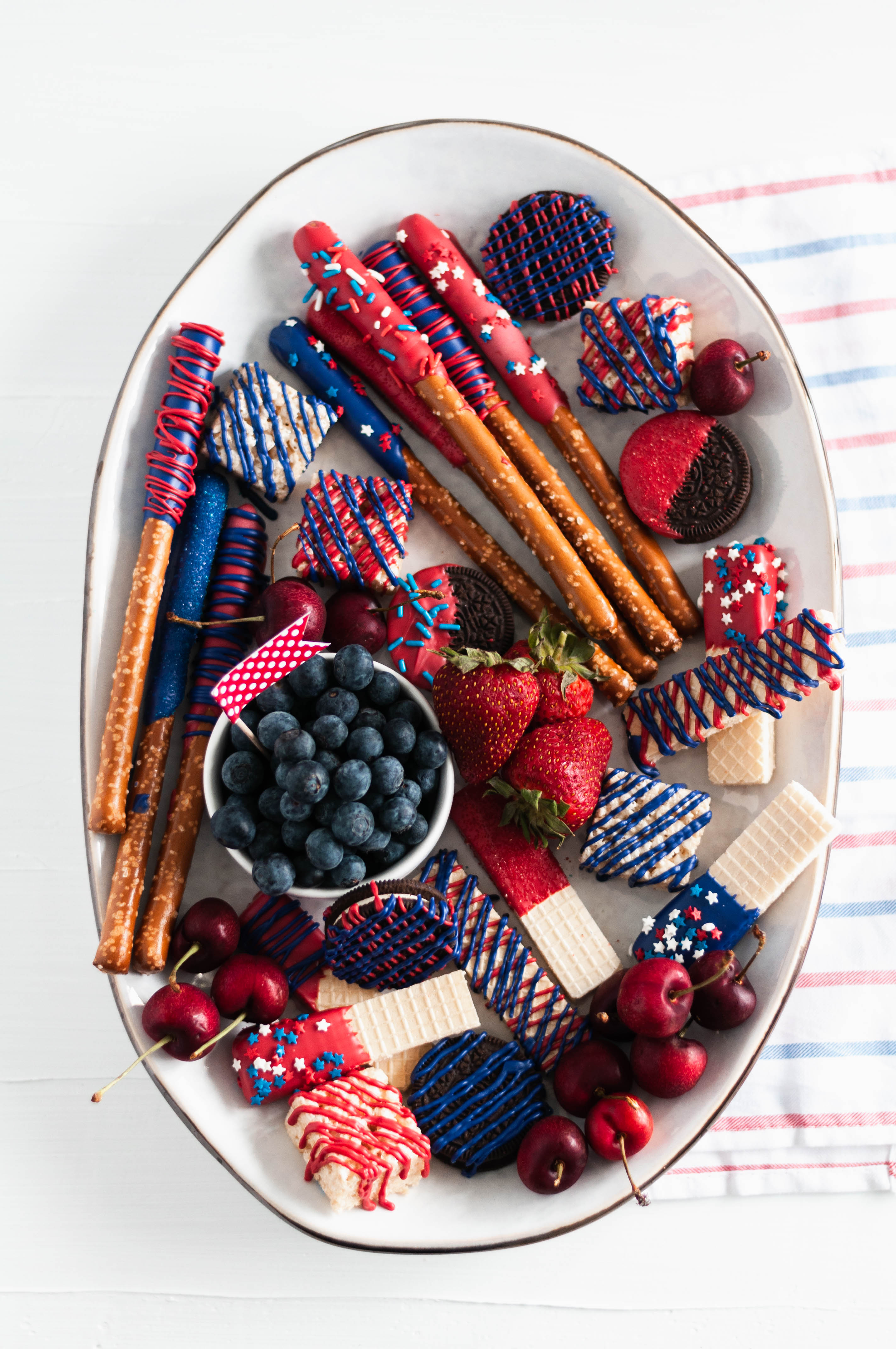 You'll be the hit of the 4th of July party when you show up with this Red White and Blue Dessert Board. Super simple to make with store-bought ingredients, some time and all your creative juices.
