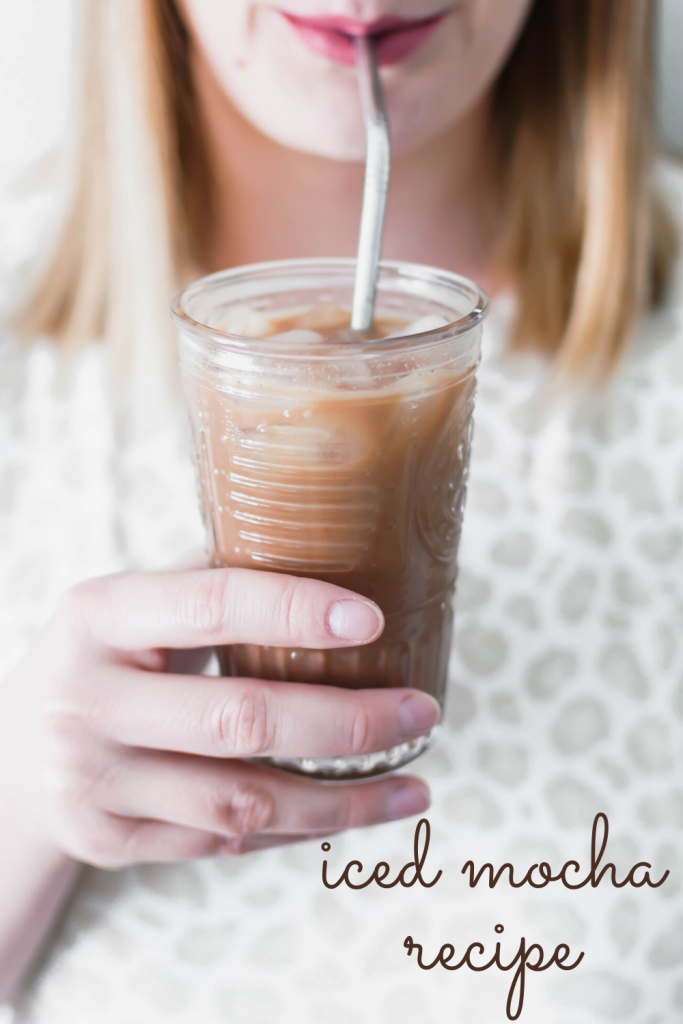 person taking a sip of homemade iced mocha recipe in a glass with a metal straw. Missing your favorite coffee shop? Try making a classic at home with this Iced Mocha Recipe. Only three ingredients required!