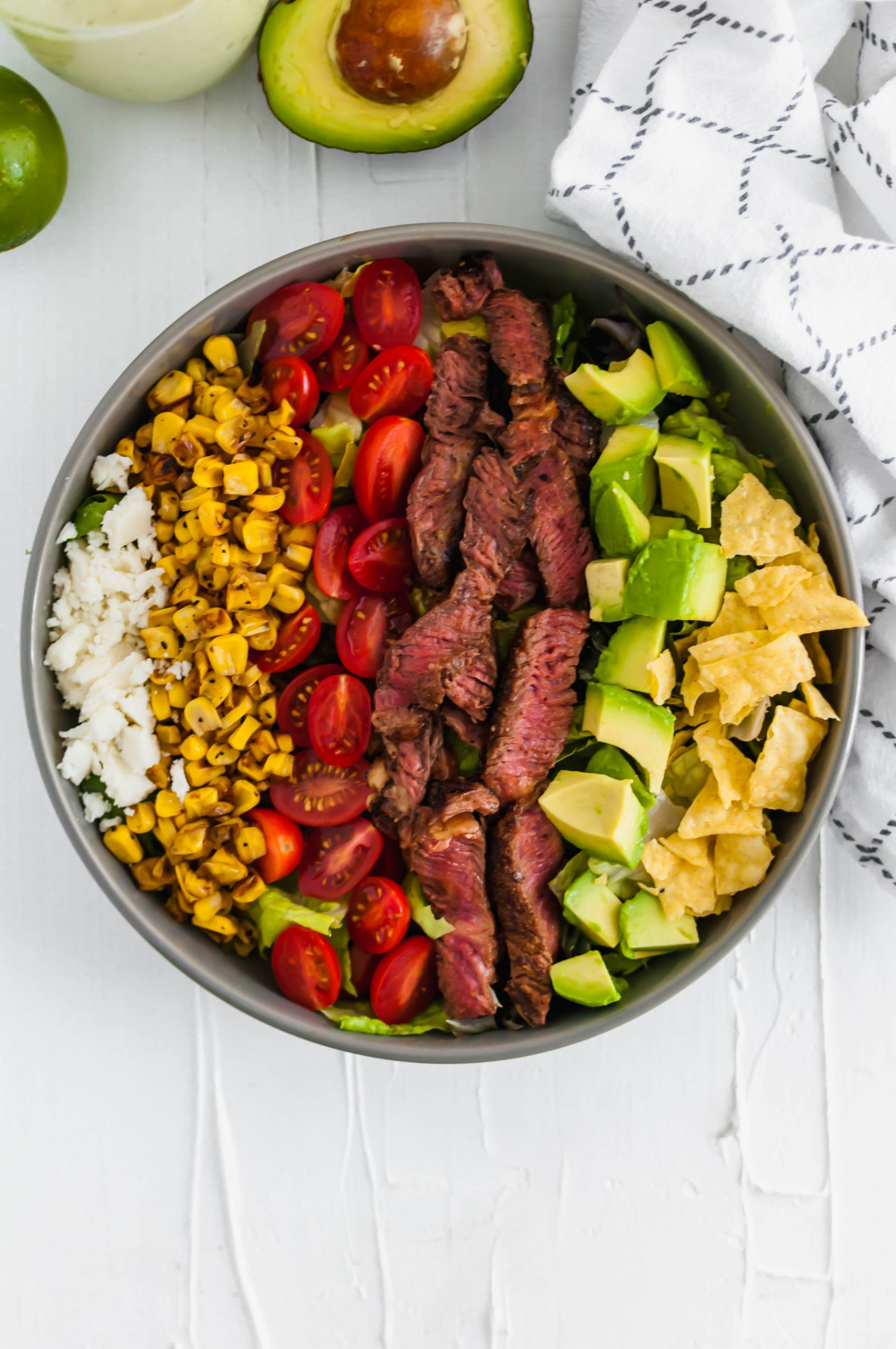 This Southwest Steak Salad is the ultimate summer salad. Packed with grilled steak, charred corn, avocado, crumbled queso fresco, tomatoes and crushed tortilla chips.