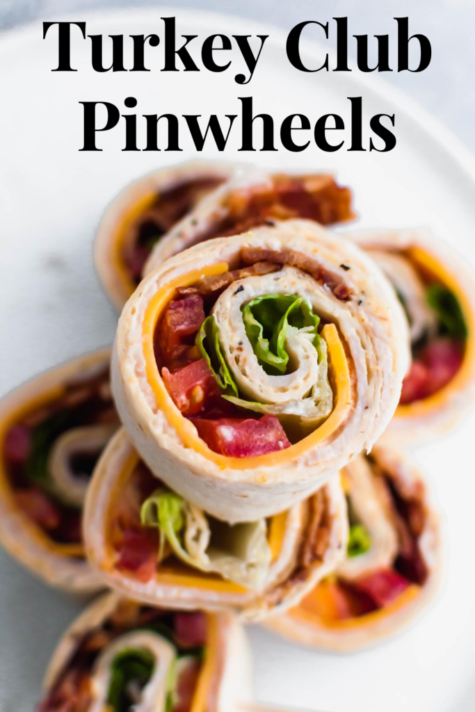 These Turkey Club Pinwheels turn the classic sandwich into a fun, bite-size appetizer. Great for parties or a fun lunch option. Spiced mayo, sharp cheddar cheese, deli turkey, bacon, lettuce and tomato make up these delicious pinwheels.