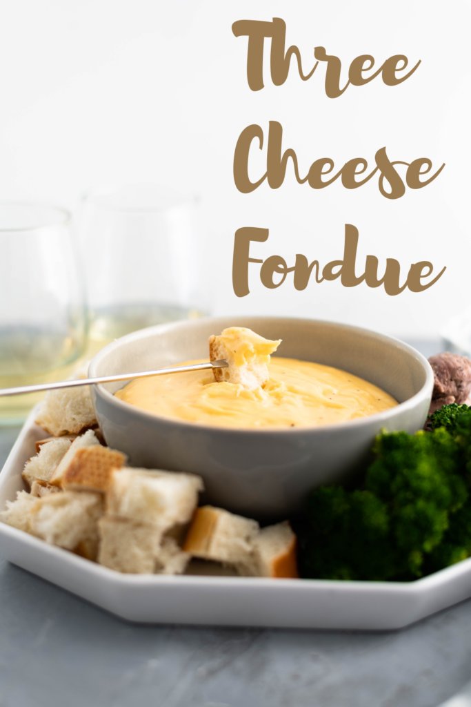 Three Cheese Fondue is perfect for the holidays. Creamy smoked gouda, sharp cheddar and fresh parmesan combine with garlic and white wine for a super fun appetizer or dinner. Use bread, steamed veggies, chicken and steak as dippers.