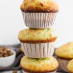 3 large bakery style pistachio muffins stacked on top of each other with bowl of pistachios in upper left corner and more muffins in upper right corner.