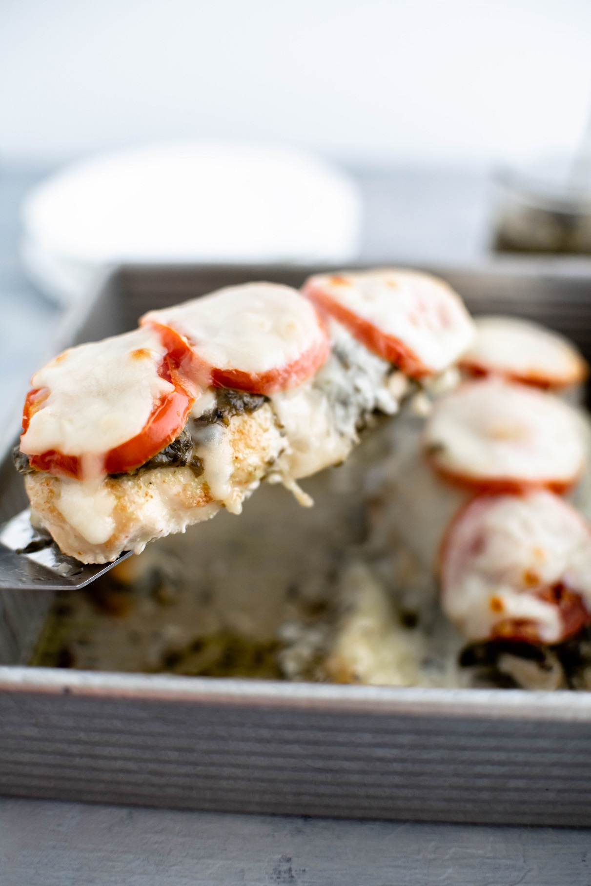Baked pesto chicken being lifted from baking dish on a small spatula.