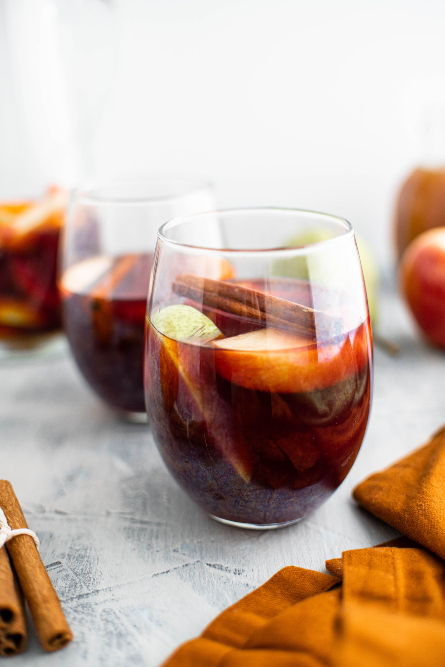 Two glasses of fall sangria with sliced apples, sliced pears, sliced oranges and a cinnamon stick floating in it. Pitcher of sangria in back left corner.