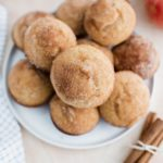 Dozen apple cider muffins piled on a round white plate with a tied bundle of cinnamon sticks in lover right corner and apples and apple cider in background.